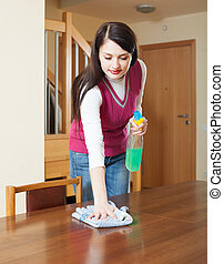long-haired girl dusting table with detergent polish at home...