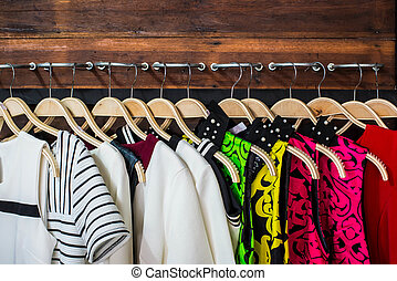 Blouses - Many blouses on hangers in the dressing room.
