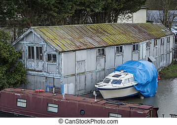 Old boat house with boats moored alongside