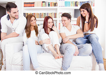 friends having conversation on sofa at home - happy friends...