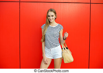 Beautiful smiling woman with a bag in front of the red wall