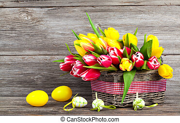 spring tulips in wooden basket with Easter eggs, on wooden...