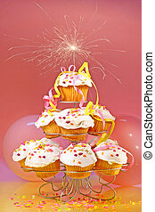 Cupcakes with sparkler on top against pink background