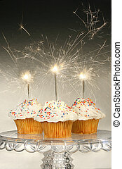 Cupcakes with sparklers on glass cake stand