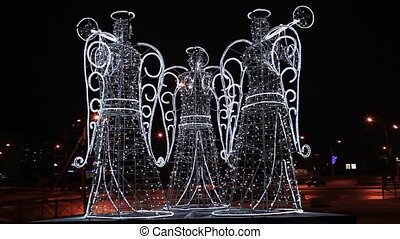 Angels in the night city - luminous figures of the three...