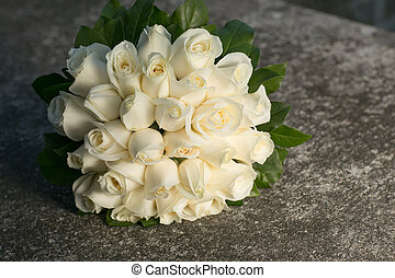 wedding bridal bouquet with white roses on stone