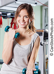 Exercises with weights - Young woman doing exercises with...