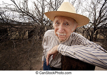 Rancher with sad eyes - Elderly rancher with sad eyes in a...