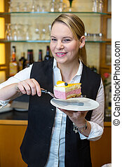 Waitress at caf? presenting cake on plate - Waitress...