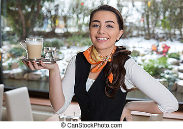 Waitress posing with cup of coffee in caf? or restaurant -...