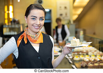 Waitress presenting cake in cafe or confectionery - waitress...