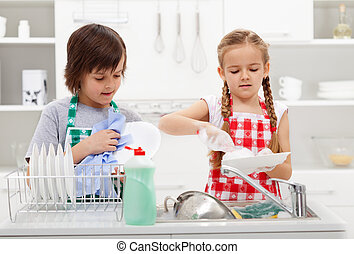 Kids washing the dishes in the kitchen together - helping...
