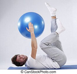 Exercises with fitness ball - Young man enjoying exercises...