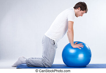 Rehabilitation exercises on fitness ball - Man doing...