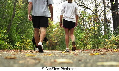 Couple walking their dog on trail. - Young couple walking...
