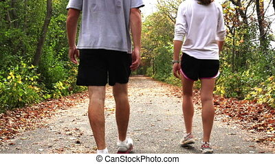 Couple walking their dog on trail - Young couple walking...