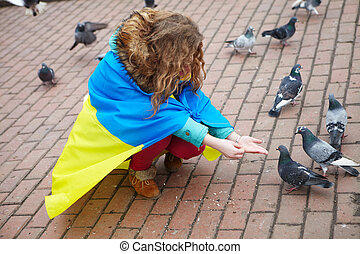 The girl with a flag feeds the pigeons on the square