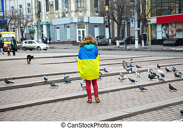 The girl with a flag stands on the square