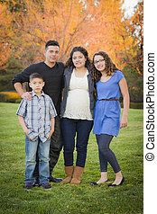 Attractive Hispanic Family Portrait in a Colorful Fall Outdoor Setting At the Park.