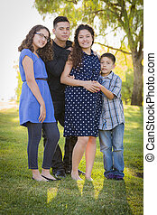 Happy Attractive Hispanic Family With Their Pregnant Mother Outdoors At the Park.