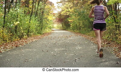 Girl jogging on trail - Young girl jogging down a walking...