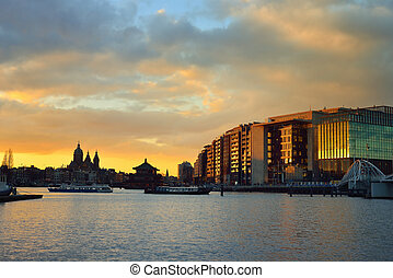 Amsterdam waterfront and skyline at sunset - The iconic...