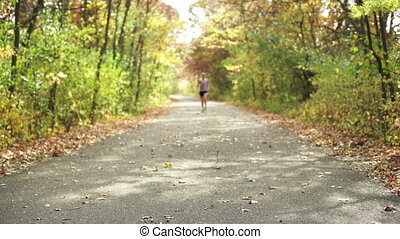 Girl jogging on trail. - Young girl jogging down a walking...