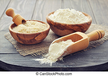 Rice flour - Raw rice and flour in bowls with scoop on...