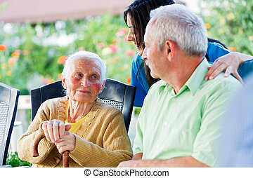 Caring for Needy - Elderly woman looking to the carer and...