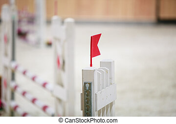 Closeup white obstacle with red flag for jumping horses...