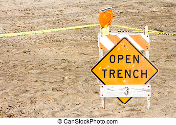 Construction site barrier, open trench warning sign in sand...