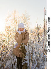 Young girl leaning on a tree in winter