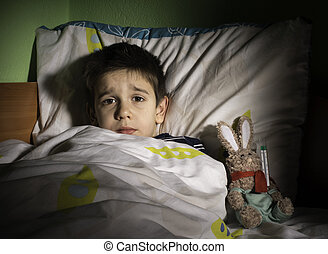 Sick child in bed with teddy bear