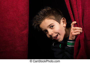Child appearing beneath the curtain. Red curtain.