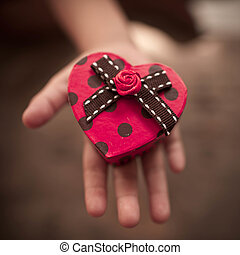 Red heart box in childs hands