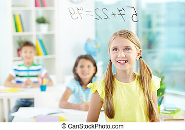 Doing sums - Portrait of lovely girl looking at sums on...