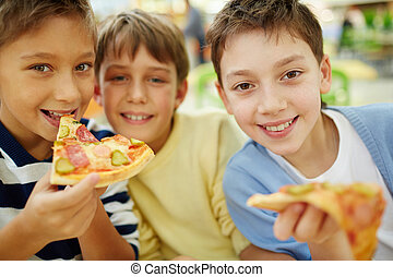Tasty refreshment - Three happy boys enjoying pizza
