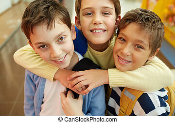Best friends - Portrait of three happy embracing boys