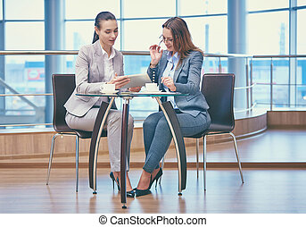 Discussion of project - Image of two friendly businesswomen...