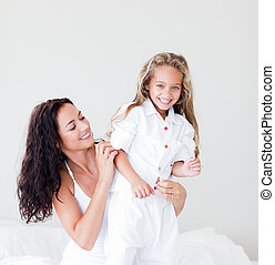 Mother and daughter on bed smiling at camera - Young Mother...