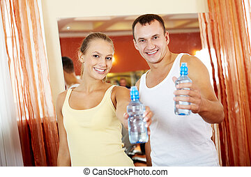 Fit couple - Portrait of happy woman and man refreshing...
