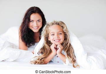 Mother and daugther embracing on bed - Young Mother and...