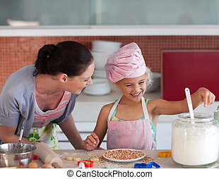 Mother teaching Child how to cook - Young mother in kitchen...