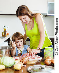 woman with little girl cooking at kitchen - woman with...