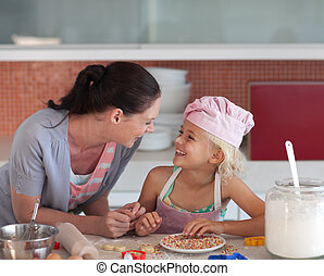 Potrait of mother and Daugther in Kitchen preparing food -...