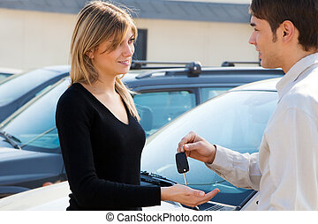 car keys - cropped view of man in car dealership giving car...