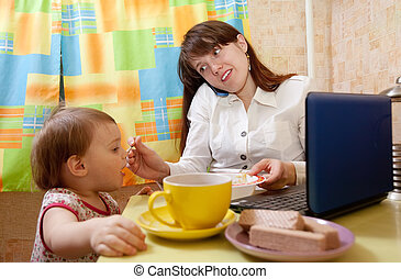 businesswoman feeding baby and speak by mobile at kitchen in...
