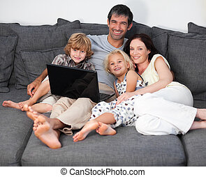 Family on a sofa with laptop - Young Family on a sofa with...