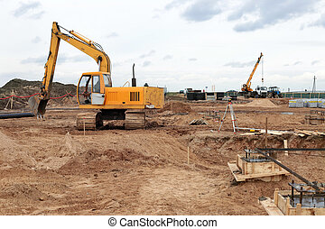 yellow excavator on a construction site - small yellow...
