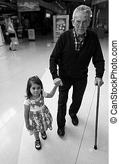 Littel girl helping and supporting her great grandfather...